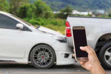 Hand of woman holding smartphone and take photo of car accident