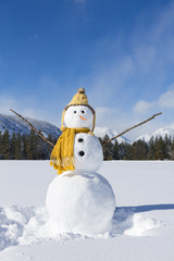 Cute fun snowman with knit hat and scarf in snowy winter landscape field with mountains and blue sky
