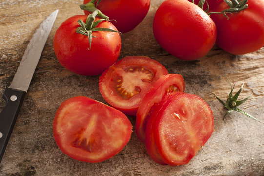 Sliced succulent red tomatoes beside serrated knife