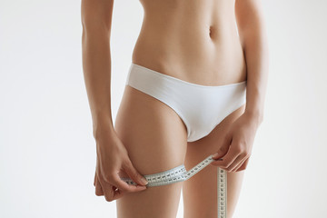 fit young woman measuring her waistline, grey blurred background with a space for your text