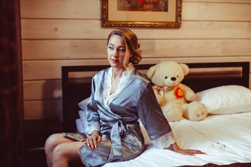 girl sitting on bed in Bathrobe