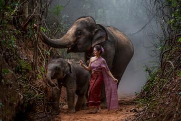 Beautiful Asian Woman wears thai dress with her elephant, elepha