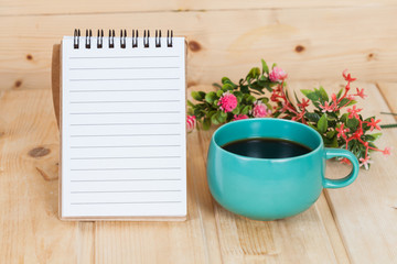 note book with cup and vase on wood table