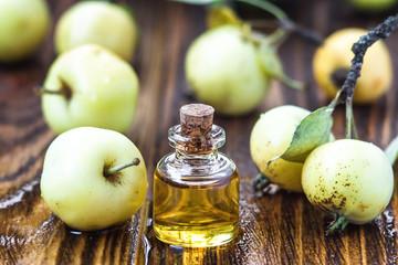 Apple vinegar in glass jar with ripe green wild apple fruits. Bottle of apple organic vinegar on wooden background. Healthy organic food.