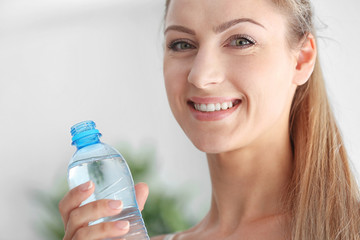 Beautiful girl drinking water on light background
