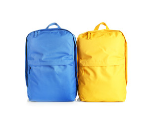 Yellow and blue backpacks on white background