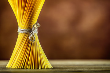 Bunch of spaghetti on wooden table -  brown background.