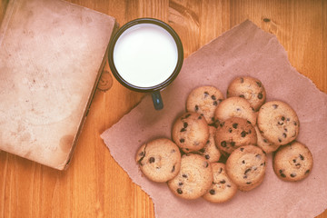 Homemade chocolate chip cookies, milk cup and vintage book