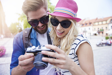 Couple looking on camera screen with pictures