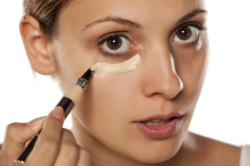 young beautiful woman applied concealer under the eyes