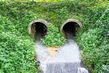 Water flowing from  drain pipe into a river