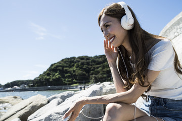 Women are listening to music with the headphones at the beach