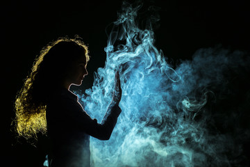 The girl stand in the fume on the dark background