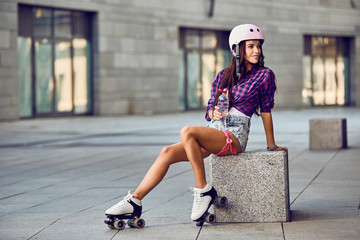 Portrait of beautiful brunette girl in helmet in urban skate park. Hipster girl drink water and resting after active time and rollerblading.