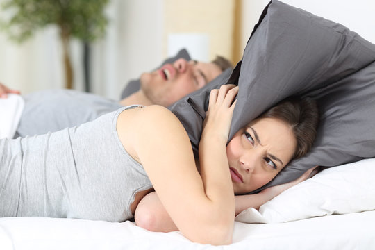 Man snoring and his wife covering ears