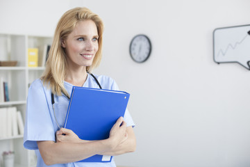 Young beautiful female doctor and practitioner working at desk