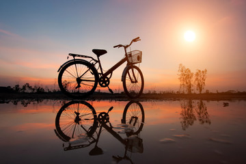 Black silhouette of a bicycle parked on the waterfront and refle