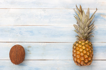 Pineapple and coconut on blue wooden board