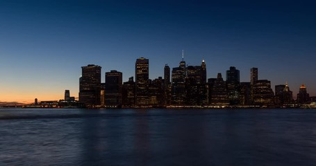 Wall Mural - New York City Lower Manhattan skyscrapers between sunset, dusk and nightfall. Time lapse cityscape view of the Financial District lights and East River with passing boats