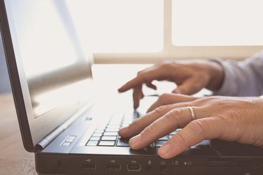 Man hands typing on keyboard laptop
