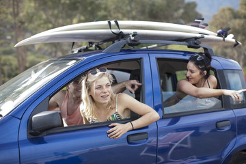Friends omn a trip in car with surfboards on roof
