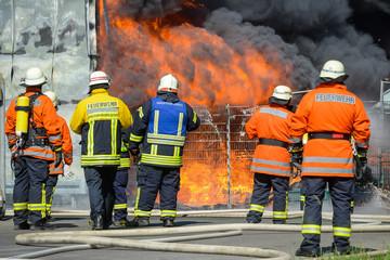 Feuerwehrmänner vor brennendem Gebäude