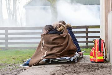 Kinder sitzen in eine Decke gehüllt vor einem brennenden Haus
