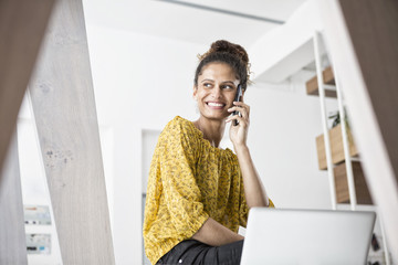 Smiling woman sitting on office desk using cell phone
