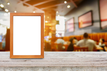 photo frame on wood table over restaurant blur background