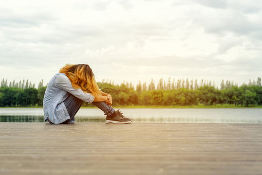 Sad woman hands off her face so sadly sitting on wood balcony by