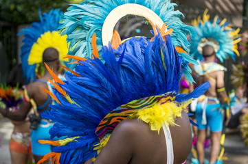 Group of carnival dancers wearing colorful feathers costumes gathered for a street parade