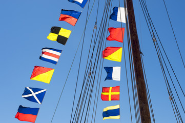 Colorful nautical sailing flags flying in the wind from the lines of a sailboat mast backlit in bright blue sky by the sun
