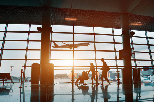 people in airport, silhouette of young family with baby traveling by plane