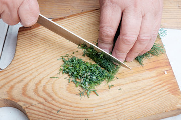 Female hands chopping dill on wooden board.