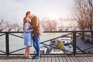 romantic date, young couple kissing on the bridge in Paris