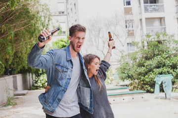 drunk people singing on the street, young couple with beers