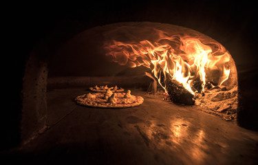 Pizza being baked in the wood oven