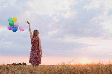 hope concept, emotions and feelings, woman with colourful balloons in the field, background