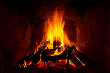 fire burning in a fireplace in a cosy, warm atmosphere, in autumn (fall) or winter