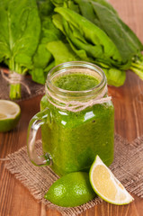 Jar mugs filled with green fresh organic spinach and lime lemon smoothie. Detox concept.