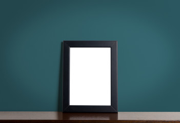 Black photo frame on wooden table with navy wall background.