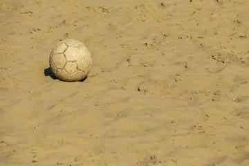 Ruined soccer ball on beach sand