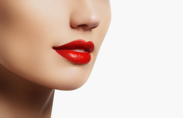 Cosmetics and makeup. Perfect lip makeup. Fashion model applying lipstick. Beautiful young woman with bright red lipstick. Beauty concept