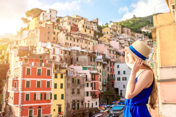 Young female traveler in blue dress enjoying great view on the old coastal town in Riomaggiore on the northern Italy