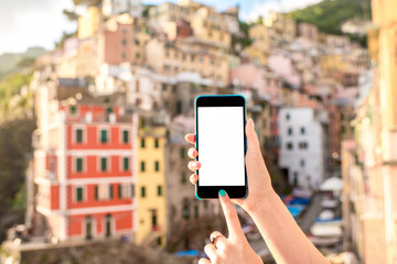 Holding smart phone with white screen on the old italian town background in Riomaggiore