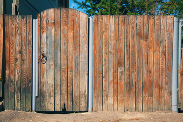 Old wooden rustic fence with a gate