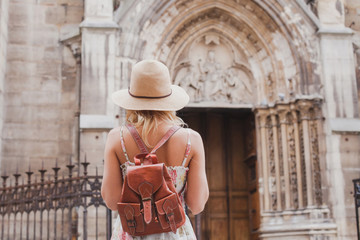 tourist travels in Europe, sightseeing tour, back of woman with backpack looking at historical architecture Fototapete