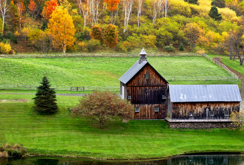 Beautiful old barn in a green meadow and colorful autumn trees