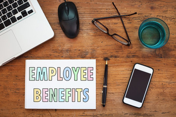 employee benefits concept, note in the notepad on wooden table