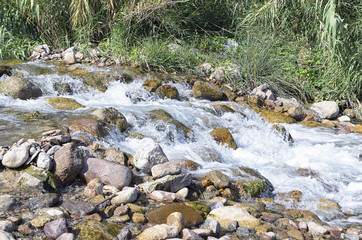 Nature background. River with strong flow, through rocks, forming little waterfalls